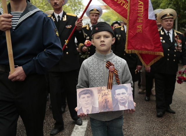 A boy wears a ribbon symbolizing the Soviet victory in World War II, as he holds portraits of relatives who served in the Red Army, during a Victory Day military parade in Sevastopol, Crimea, Friday, May 9, 2014. President Vladimir Putin hailed the return of Crimea to Russia in his first visit to the region since its annexation by Moscow in March. (Photo by Ivan Sekretarev/AP Photo)