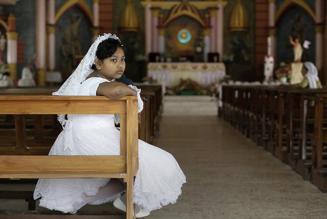 An Indian Christian girl waits for a ceremony at a Church on Easter Sunday in Gauhati, India, Sunday, April 16, 2017. Christians make up about 2.3 percent of India's population of 1.26 billion. (Photo by Anupam Nath/AP Photo)