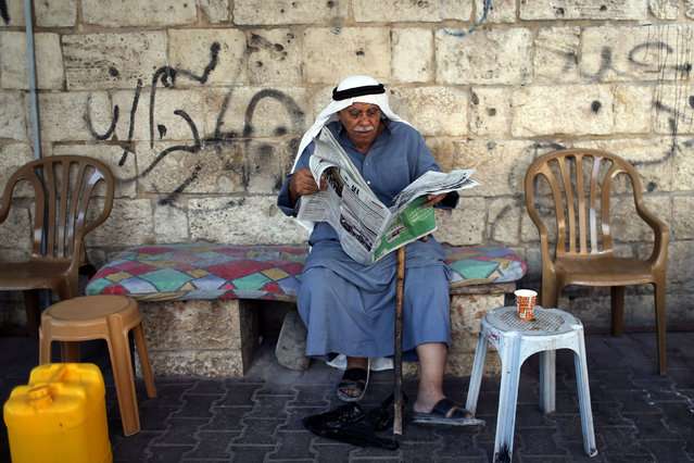A Palestinian man reads a newspaper featuring news on the Israel's parliamentary election, in the southern Gaza Strip on September 18, 2019. (Photo by Ibraheem Abu Mustafa/Reuters)