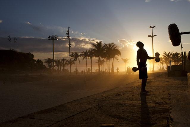 A man works out at sunset at the Arpoador beach in Rio de Janeiro, Brazil, Friday, December 16, 2011. (Photo by Felipe Dana/AP Photo)