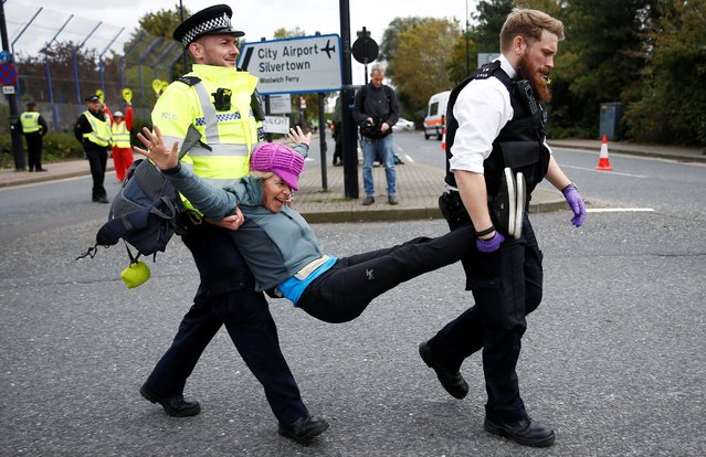 Police officers detain an Extinction Rebellion protester during a demonstration, near London City Airport, in London, Britain, October 10, 2019. (Photo by Henry Nicholls/Reuters)