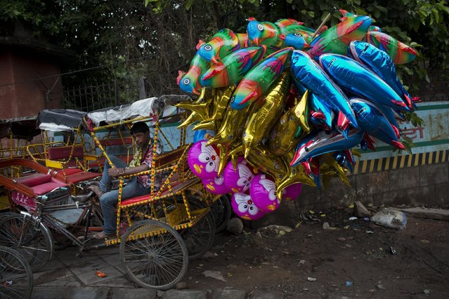 A bicycle rickshaw driver guards balloons outside the Jama Masjid mosque in New Delhi, India, Saturday, July 18, 2015. (Photo by Bernat Armangue/AP Photo)