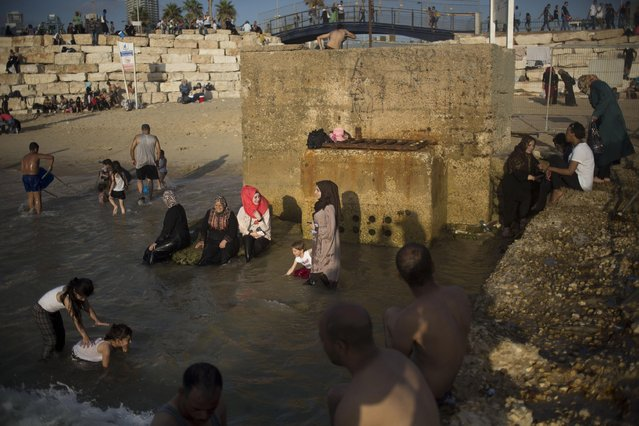Muslims, many of whom are Palestinians from the West Bank, bathe in the Mediterranean Sea during the last day of the Eid al-Fitr holiday as the sun sets in Tel Aviv, Israel, Sunday, July 19, 2015. (Photo by Ariel Schalit/AP Photo)