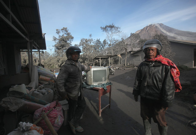 Villagers gather their belongings to evacuate their homes to a safe zone following the eruption of Mount Sinabung in Gamber village, North Sumatra, Indonesia, Sunday, May 22, 2016. (Photo by Binsar Bakkara/AP Photo)