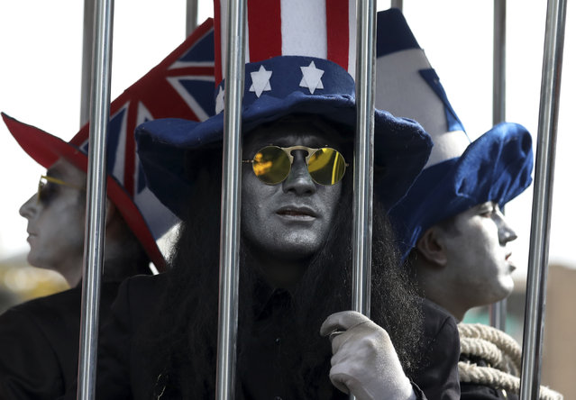 "Actors wear hats colored in the flags of the United States, Israel, and Britain imprisoned in a cage during the anti-U.S. annual rally in front of the former U.S. Embassy in Tehran, Iran, Monday, November 4, 2019. Reviving decades-old cries of ""Death to America"", Iran on Monday marked the 40th anniversary of the 1979 student takeover of the U.S. Embassy in Tehran and the 444-day hostage crisis that followed as tensions remain high over the country's collapsing nuclear deal with world powers. (Photo by Vahid Salemi/AP Photo)"