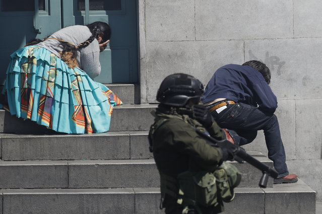 Pedestrians take cover from tear gas launched by security forces at anti-government demonstrators in La Paz, Bolivia, Thursday, November 21, 2019. Backers of former President Evo Morales have taken to the streets asking for his return since he resigned on Nov. 10 under pressure from the military after weeks of protests against him over a disputed election he claim to have won. (Photo by Natacha Pisarenko/AP Photo)