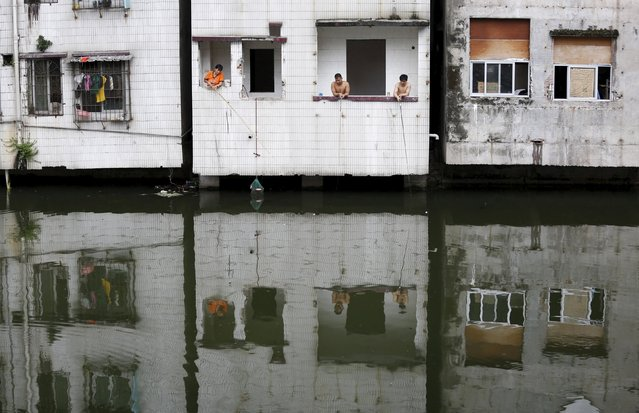 People fish at an abandoned flat in Xian village, a slum area in downtown Guangzhou, China July 24, 2015. (Photo by Tyrone Siu/Reuters)