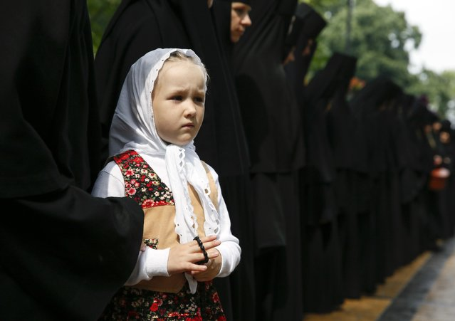 A girl stands next to nuns during a ceremony marking the 1,000th anniversary of the death of Vladimir the Great in Kiev, Ukraine, July 27, 2015. (Photo by Valentyn Ogirenko/Reuters)