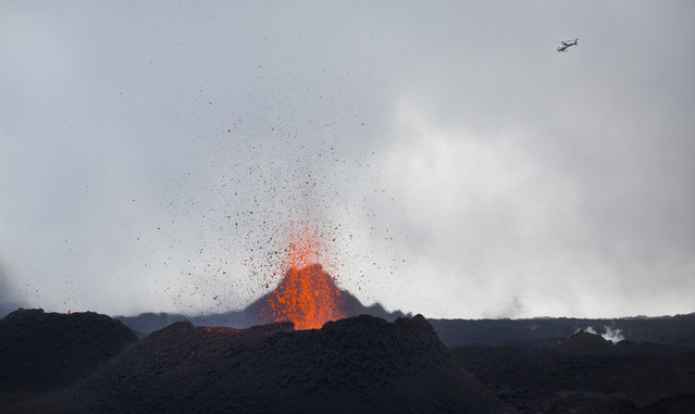 "A helicopter flies over as lava erupts from the Piton de la Fournaise ""Peak of the Furnace"" volcano, on the southeastern corner of the Indian Ocean island of Reunion Saturday, August 1, 2015. (Photo by Ben Curtis/AP Photo)"