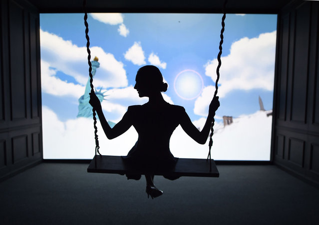 "A woman tries a swing in front of a screen featuring New York scenes during the new Air France Exhibition called ""Air France, France is in the Air"" in New York June 25, 2014. (Photo by Timothy A. Clary/AFP Photo)"