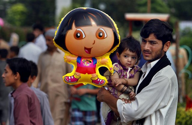 A Pakistani man carries his daughter with a balloon as his family visit a park in Rawalpindi, Pakistan, Tuesday, July 21, 2015. (Photo by Anjum Naveed/AP Photo)
