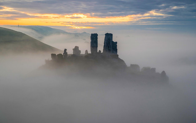 The sun begins to rise behind a mist covered Corfe Castle in Dorset, England on October 22, 2019. (Photo by Andrew Matthews/PA Images via Getty Images)