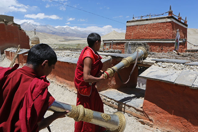 Monks set up dungchen, Tibetan ritual horns, on a monastery rooftop at the end of a ceremony during the Tenchi Festival on May 25, 2014 in Lo Manthang, Nepal. The Tenchi Festival takes place annually in Lo Manthang, the capital of Upper Mustang and the former Tibetan Kingdom of Lo. Each spring, monks perform ceremonies, rites, and dances during the Tenchi Festival to dispel evils and demons from the former kingdom. (Photo by Taylor Weidman/Getty Images)