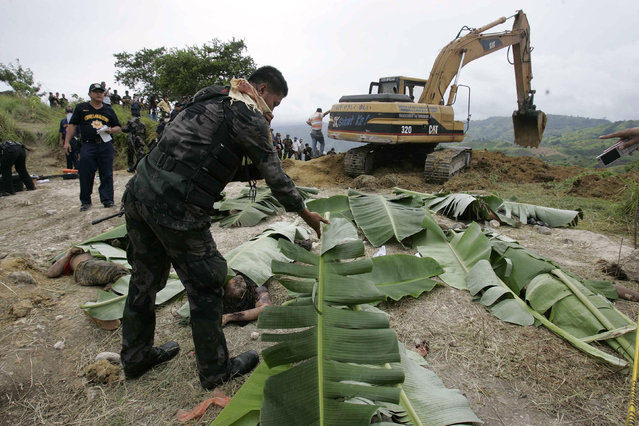 In this November 24, 2009, file photo, a police officer uses banana leaves to cover bodies which they recovered from a hillside grave in Datu Ampatuan, Maguindanao province, southern Philippines. A Philippine court will rule Thursday, Dec. 19, 2019 whether scions of a political clan and their gunmen are guilty of slaughtering 58 people, including 32 media workers, in an act of impunity that horrified the world. (Photo by Aaron Favila/AP Photo/File)