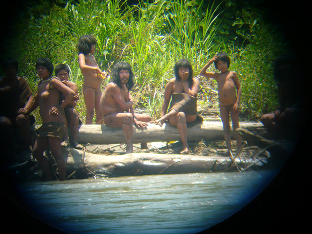 Members of the Mashco-Piro tribe observe a group of travelers from across the Alto Madre de Dios river in the Manu National Park in the Amazon basin of southeastern Peru, as photographed through a bird scope October 21, 2011. Survival International has the Mashco-Piro tribe listed as one of around 100 uncontacted indigenous tribes in the world. (Photo by Jean-Paul Van Belle/Reuters)