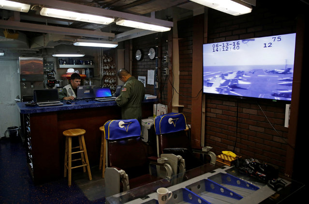 """Pilots with the VAW-117 """"Wallbangers"""" Airborne Command squadron wait in their room on board the USS Harry S. Truman aircraft carrier in the eastern Mediterranean Sea, June 13, 2016. (Photo by Baz Ratner/Reuters)"""