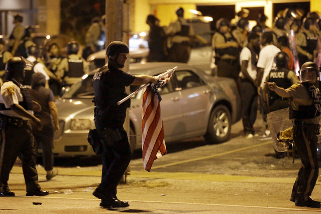 An officer holds a flag he took from a protestor, Monday, August 10, 2015, in Ferguson, Mo. (Photo by Jeff Roberson/AP Photo)