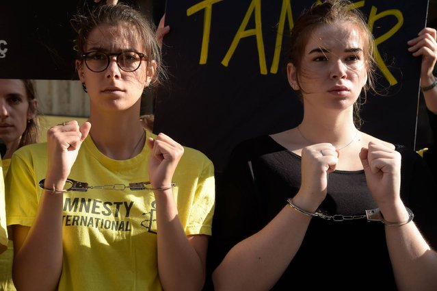 """Activists from human rights NGO Amnesty International stand with their hands handcuffed during a protest outside the Turkish Embassy in Paris on July 20, 2017 to call for the release of human rights defenders jailed in Turkey. Amnesty International on July 18, 2017 called on world leaders to pressure Turkey into releasing six human rights activists accused of aiding """"terror"""" groups, saying the country was turning """"increasingly rogue"""". (Photo by Bertrand Guay/AFP Photo)"""