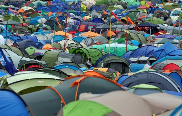Revellers walk near tents at Worthy Farm in Somerset during the Glastonbury Festival, Britain June 23, 2016. (Photo by Stoyan Nenov/Reuters)