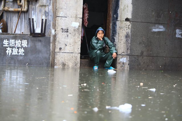 A woman looks on at a flooded area in Changsha, central China's Hunan province, on July 15, 2014. The meteorological department in Hunan issued an orange alert for storm, as heavy rain hits the province's central and northern area, local media reported. (Photo by AFP Photo)