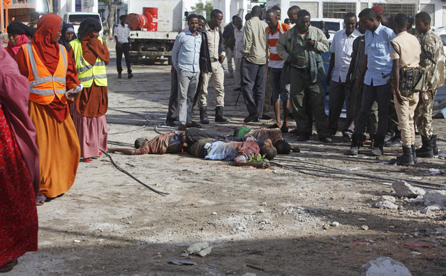 Somali soldiers and people gather around dead bodies of suspected al-Shabab who had attacked Nasa-Hablod hotel in Mogadishu, Somalia, Sunday, June 26, 2016. Islamic extremist group al-Shabab claimed responsibility for the latest in a series of hotel attacks in Mogadishu, one that began with a powerful explosion at the entry gate. (Photo by Farah Abdi Warsameh/AP Photo)