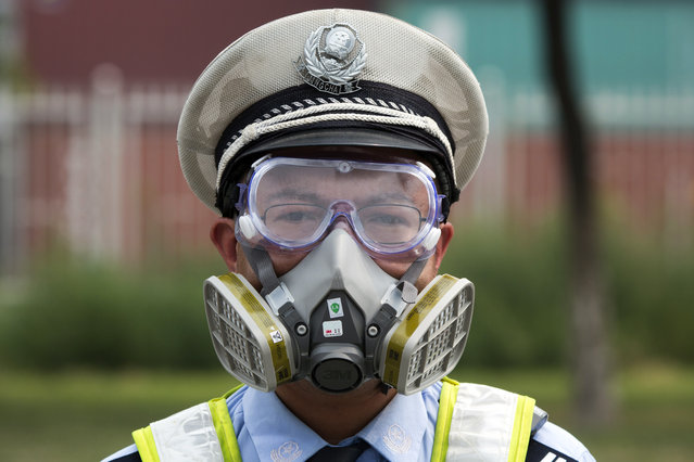 A Chinese traffic police man wears a mask at a security checkpoint near the site of an explosion in northeastern China's Tianjin municipality Saturday, August 15, 2015. (Photo by Ng Han Guan/AP Photo)