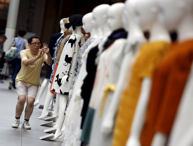 A man takes pictures of creations displayed during Tokyo Fantashion at a shopping district in Tokyo, Japan, August 16, 2015. (Photo by Yuya Shino/Reuters)