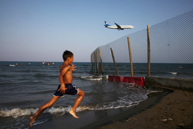 A boy runs on a beach while an airplane prepares to land at Larnaca International Airport, Cyprus June 28, 2016. (Photo by Yiannis Kourtoglou/Reuters)
