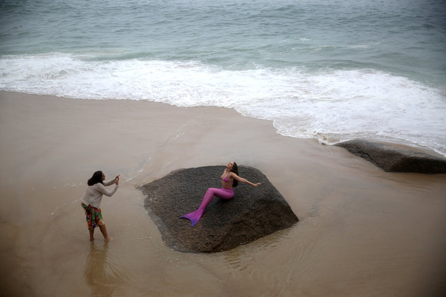 A woman takes a photograph of a girl as she participates in a mermaid lesson in Rio de Janeiro, Brazil, May 28, 2017. (Photo by Pilar Olivares/Reuters)