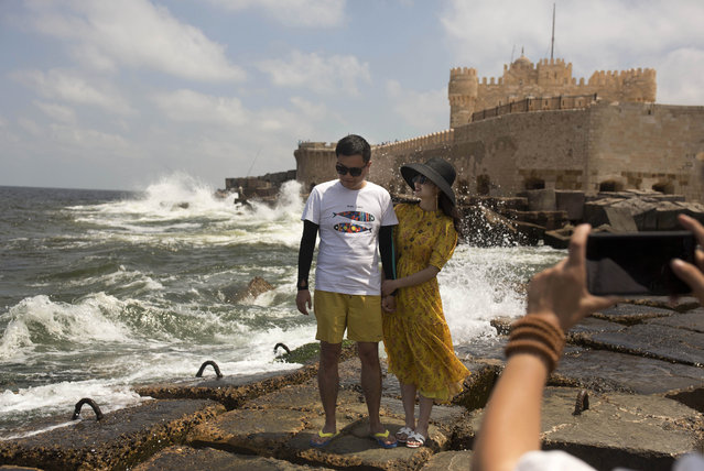 In this August 8, 2019, photo, a couple poses for a portrait on cement blocks placed as reinforcement against rising water levels near the citadel in Alexandria, Egypt. Egypt's coastal city of Alexandria, which has survived invasions, fires and earthquakes since it was founded by Alexander the Great more than 2,000 years ago, now faces a new menace from climate change. Rising sea levels threaten to inundate poorer neighborhoods and archaeological sites, prompting authorities to erect concrete barriers out at sea to hold back the surging waves. (Photo by Maya Alleruzzo/AP Photo)
