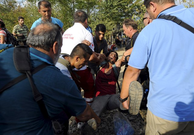 Members of the media carry a man who collapsed at the border line dividing Macedonia and Greece August 21, 2015. (Photo by Ognen Teofilovski/Reuters)