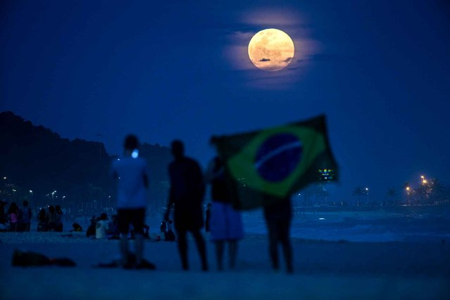 """The full moon, nicknamed """"the supermoon"""", rises at Ipanema beach in Rio de Janeiro, Brazil, on August 10, 2014. A supermoon is the coincidence of a full moon or a new moon with the closest approach the Moon makes to the Earth on its elliptical orbit, resulting in the largest apparent size of the lunar disk as seen from Earth. (Photo by Yasuyoshi Chiba/AFP Photo)"""