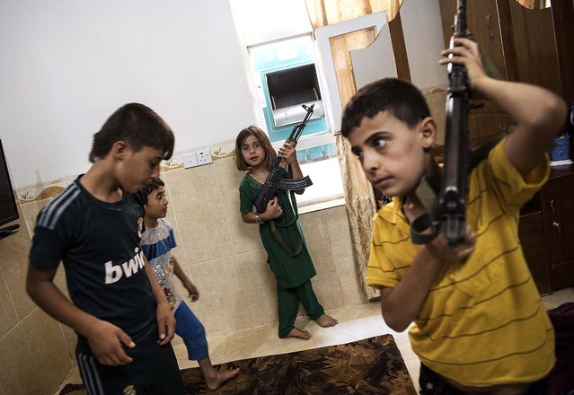 The children of Saman Babita play with the guns and protective gear he has prepared in case fighters with the Islamic State in Iraq and Syria return to Mahmour, Iraq, on August 15, 2014. (Photo by Lynsey Addario/The New York Times)