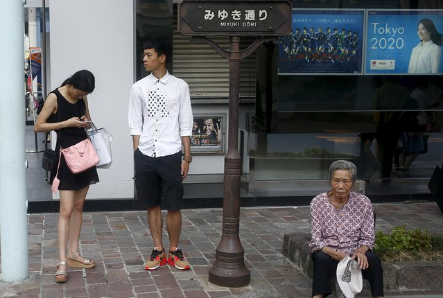 Tourists rest in the shade outside a Mizuho bank branch advertising its partnership with the Tokyo 2020 Olympic Games in the Ginza shopping districts in Tokyo, August 3, 2015. (Photo by Thomas Peter/Reuters)