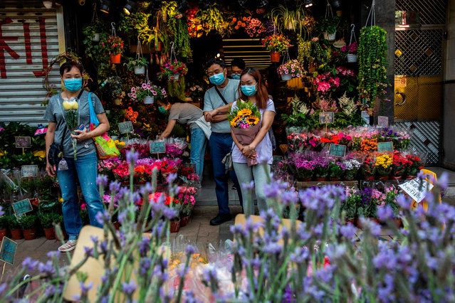 People wearing face masks, amid concerns over the spread of the COVID-19 novel coronavirus, shop for plants and flowers in Hong Kong on March 22, 2020. (Photo by Isaac Lawrence/AFP Photo)