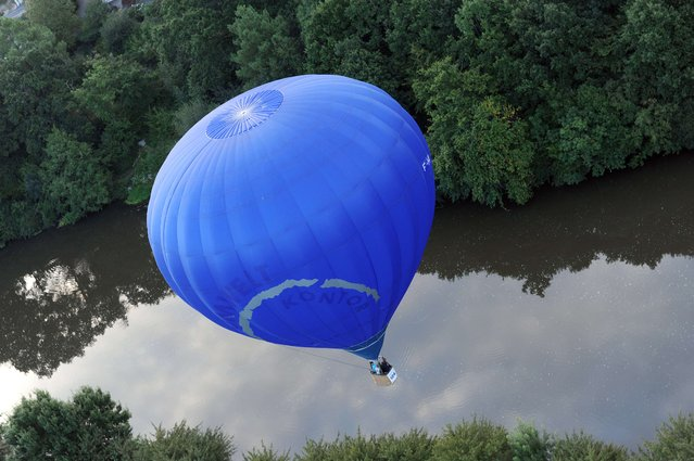 A hot air balloon flies over the Sarthe river during the 40th French Hot Air Balloon Championship on August 20, 2014, in Sable-sur-Sarthe, western France. 47 hot-air balloons compete until August 23. (Photo by Jean-Francois Monier/AFP Photo)