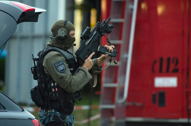Police officer search a residential area near the Olympia shopping centre after a shooting was reported there in Munich, southern Germany, Friday, July 22, 2016. Several people have been reported to be killed. (Photo by Matthias Balk/DPA via AP Photo)
