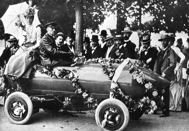 "Laurels for Camille Jenatzy (in driver's seat), the first man to exceed 100 kph (62 mph) at Acheres, near Paris. The car, christened ""Jamais Contente"", was an electric vehicle of his own design, 1899."