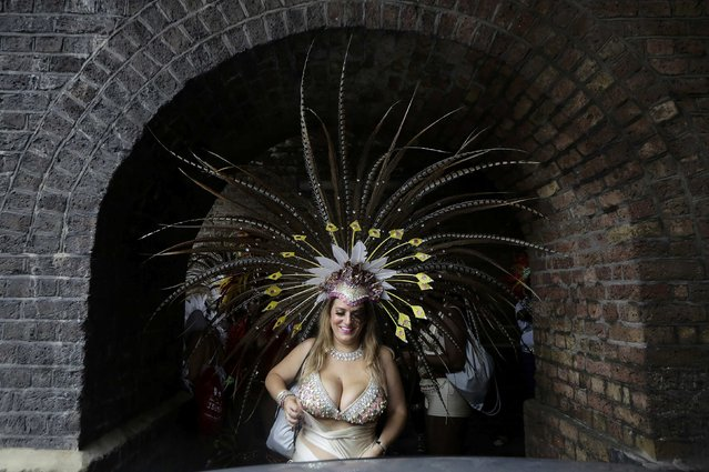 Sasha Hudson from Romford in Essex adjusts her costume under a railway arch at the Notting Hill Carnival in London August 25, 2014. (Photo by Kevin Coombs/Reuters)