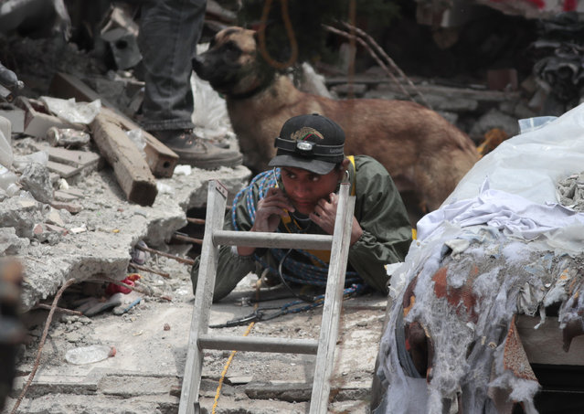 A rescue worker listens for signs of a person trapped under the rubble of a building felled by a 7.1 magnitude earthquake, in the Ciudad Jardin neighborhood of Mexico City, Thursday, September 21, 2017. (Photo by Eduardo Verdugo/AP Photo)