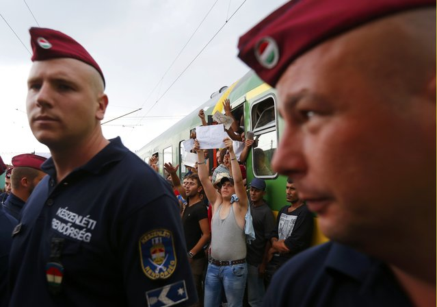 Hungarian policemen stand in front of a train with migrants at the railway station in the town of Bicske, Hungary, September 3, 2015. Migrants threw themselves onto railway lines and scuffled with helmeted riot police trying to take them to a reception center in Hungary on Thursday, forced from a train in desperate scenes symbolic of a European asylum system brought to breaking point. (Photo by Laszlo Balogh/Reuters)