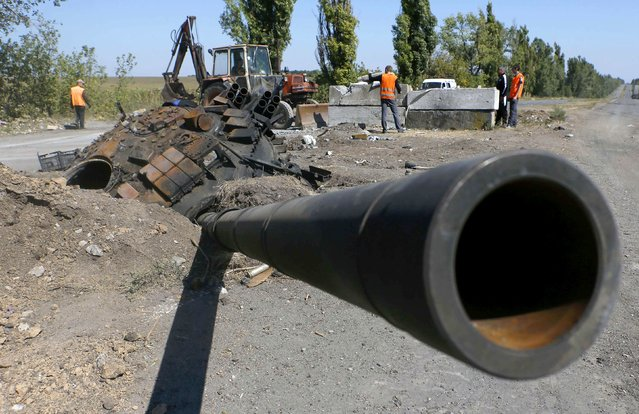 A turret with a gun from a Ukrainian army tank is pictured at the site of a destroyed Ukrainian check-point as road workers clear debris outside the town of Olenivka near the city of Donetsk, eastern Ukraine, September 2, 2014. (Photo by Maxim Shemetov/Reuters)