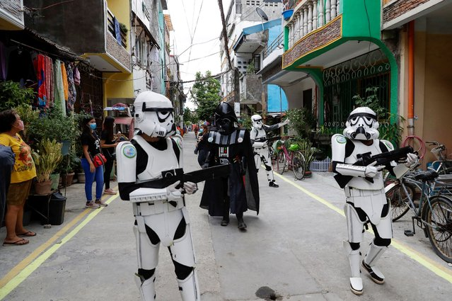 Members of a youth group in Star Wars costumes entertain locals along a road in Malabon, Metro Manila, Philippines, Thursday, April 30, 2020. The youth group walks along streets to give residents some form of entertainment as they endure the continued community quarantine and to remind them to stay at home to prevent the spread of the new coronavirus. (Photo by Aaron Favila/AP Photo)