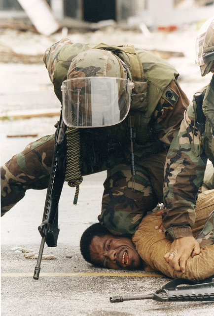 Members of the Florida National Guard subdue a man outside the Cutler Ridge shoe store after the guard found the store wide open, 2012.  The unidentified man, carrying a firearm, was wrestled to the ground after guard members though he was looting the store. There was no evidence he was looting. (Photo by Lynne Sladky/AP Photo)