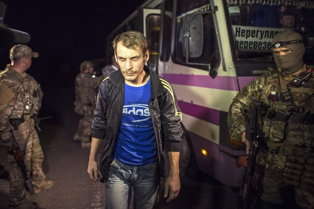 A member of the pro-Russian rebels, who is a prisoner-of-war (POW), walks in front of a bus he is about to be exchanged, north of Donetsk, eastern Ukraine, September 12, 2014. The two sides, that of the government forces and the pro-Russian separatists are exchanging POWs under the terms of the current ceasefire. (Photo by Marko Djurica/Reuters)