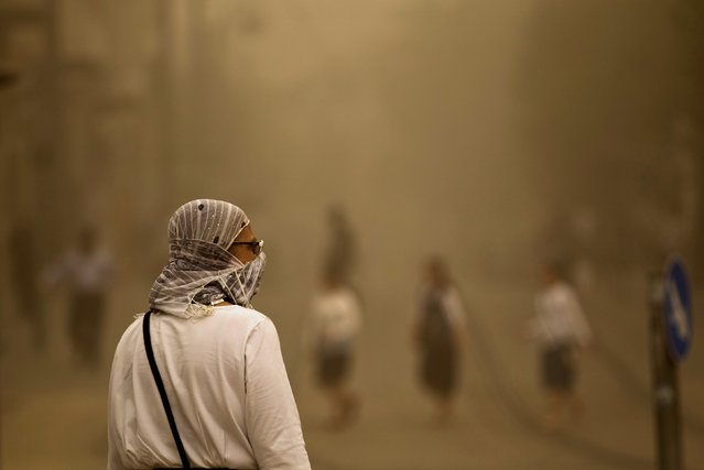 A pedestrian walks with a covered face during a sandstorm in Jerusalem September 8, 2015. (Photo by Ronen Zvulun/Reuters)
