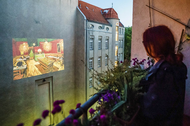 """Resident Constanze Obst watches the movie """"Loving Vincent"""" as a projection on a facade from a balcony in Berlin, Germany, 14 May 2020. The interdisciplinary artists group 'Meta Grey' projects movies on facades while cinemas are still closed to the public, due to the pandemic crisis of the SARS-CoV-2 coronavirus which causes the Covid-19 disease. (Photo by Clemens Bilan/EPA/EFE/Rex Features/Shutterstock)"""