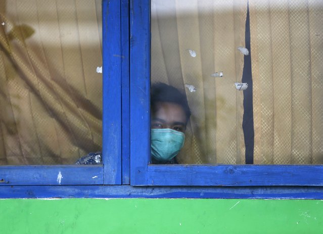 A student wearing a face mask looks out from a window of his classroom in Palembang, on Indonesia's Sumatra island September 10, 2015. Indonesia is investigating 10 firms over worsening forest fires that have created a blanket of smog over Southeast Asia, threatening them with sanctions if they are found responsible, a government minister said on Tuesday. (Photo by Reuters/Beawiharta)