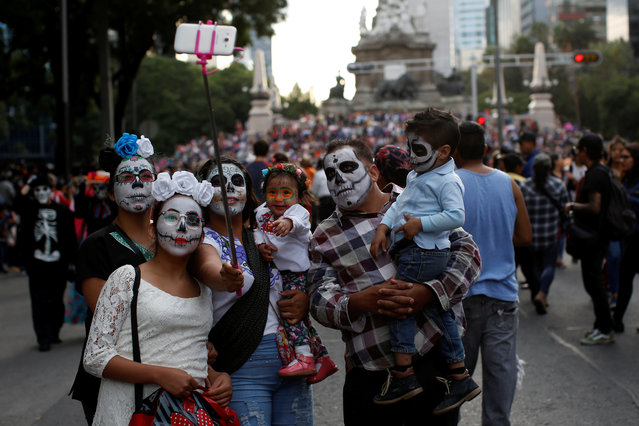 """A family dressed up as """"Catrin and Catrina"""", a Mexican character also known as """"The Elegant Death"""", take a selfie during the Catrinas parade in Mexico City, Mexico on October 22, 2017. (Photo by Carlos Jasso/Reuters)"""