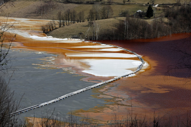 A polluted lake, tainted with cyanide and other chemicals, is seen covering Geamana village near Rosia Montana, central Romania, March 24, 2014. The sight of a nearby tailings pond that is the product of a decades-old industrial project, has been used by protesters to highlight fears about the potential fallout of the proposed gold mine. (Photo by Bogdan Cristel/Reuters)